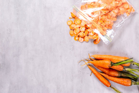 Frozen carrot in plastic bag on concrete background. Top view with copy space