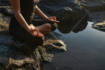 Woman practicing yoga and meditation in lotus position on black stones near the sea.