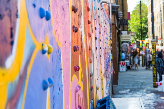 Colourful street art on the steel truss of an overpass on London's vibrant Brick Lane