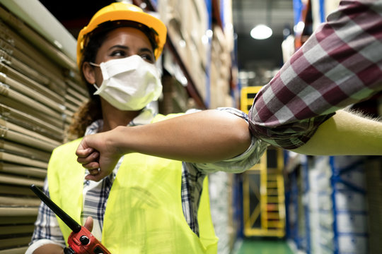 Two colleague workers in warehouse have a greeting by touching elbow.