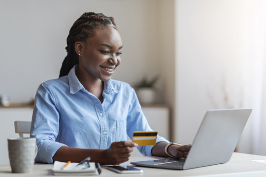 Young black businesswoman shopping online with laptop in office, using credit card