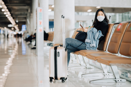 Asian woman tourist wearing face mask sitting on social distancing chair with luggage at airport terminal during coronavirus or covid-19 outbreak . New normal travel at airport