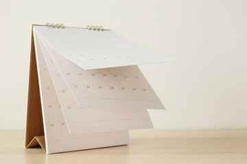 Calendar page flipping sheet on wood table background business schedule planning appointment...