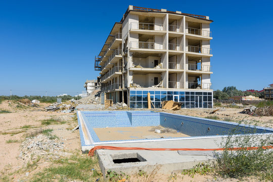 Illegal construction on the coastal side, hotel demolition, unfinished swimming pool in the foreground