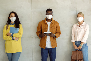 Multi-ethnic group of college students with protective face masks against the wall.