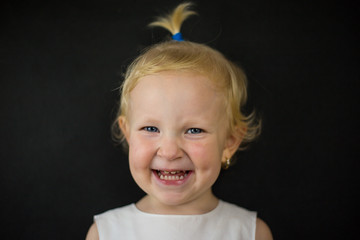 little girl on a black background with a sincere childish smile, blue eyes and blonde hair