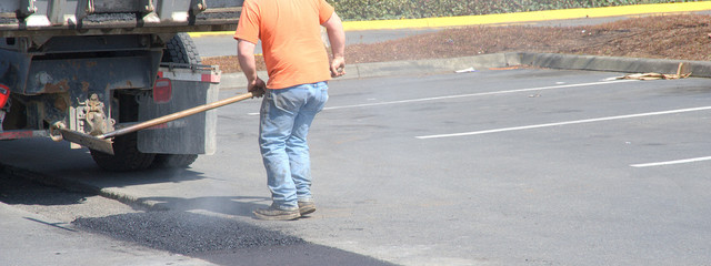 Worker repairing potholes on the street outside.