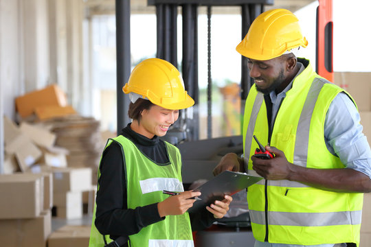 African American and Asian workers wearing safety vest while working in warehouse checking for the inventory using digital tablet