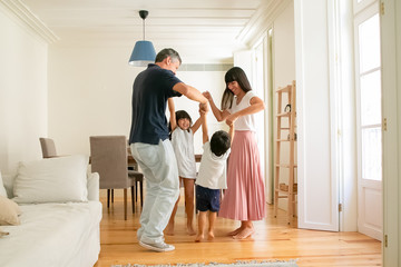 Cheerful parents and cute children playing and dancing in ring together. Pretty mother and grey-haired father holding kids hands and standing in living room. Family time, fun and weekend concept
