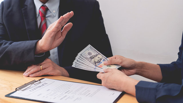 Confident businessman manager rejecting an offer of money to agreement contract from partner or refusing to take bribe, Bribery and corruption concept.
