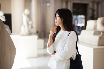 Positive chinese girl with interest looking around at ancient sculptures in museum