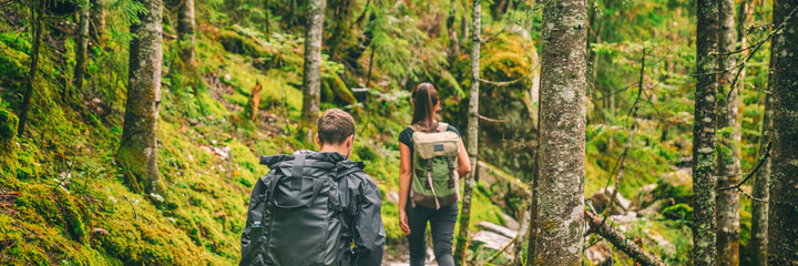 Hikers walking in forest trek banner. Couple hiking trail in autumn nature going camping with backpacks. Friends woman and man on mountain in Quebec travel, Canada.
