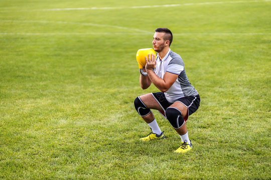 Dedicated attractive soccer player in shape doing squat endurance with kettle bell.