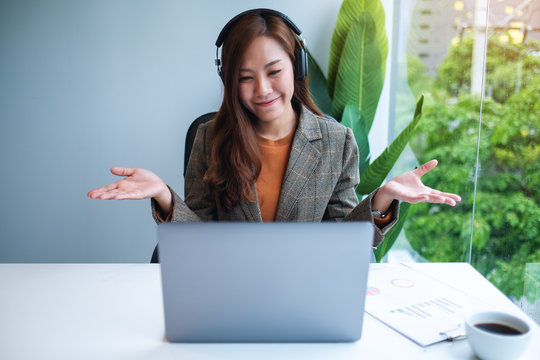 Closeup image of a beautiful businesswoman using headphone for video conference on laptop computer while working online