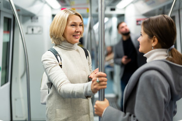 Portrait of mature woman talking friendly with her fellow traveler in modern subway car..