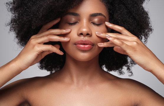 Ethnic woman applying cream on face