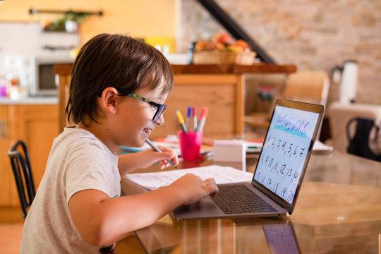 Little boy doing homework on laptop at home.