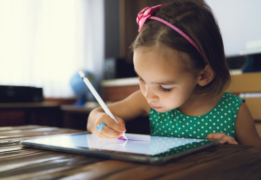 Child Girl Is Drawing And Painting Pictures Using Digital Tablet
