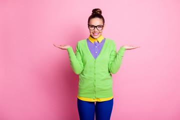 Photo of attractive cute teen girl knot hairdo hold palms empty space advice choice two equal options beaming smiling wear spectacles colored clothes bright pink color background