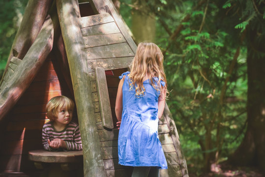 Kids playing outside at a play area with wooden toy house