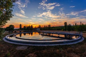 Modern sewage treatment plant. Round wastewater purification tanks at sunset.