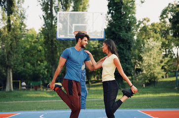 Beautiful young couple enjoying together and playing on basketball court. Bright sunny summer day.