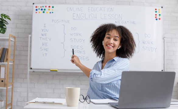 Modern education remotely. Cheerful african american woman points to blackboard and explains rules of english