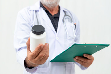 Physician medicine doctor or pharmacist sitting holding or showing bottle of pills in hand and writing prescription on special form. Medical care, pharmacy or health insurance concept