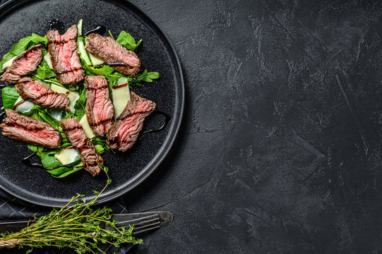Steak salad with spinach, arugula and sliced beef marbled steak. Black background. Top view. Copy space
