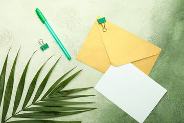 Blank card with envelope and stationery on color background
