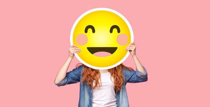 Redhead girl hiding her face behind happy emoji smile