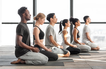 Happy multiracial men and woman practicing yoga and meditating together in studio