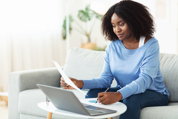 Black woman signing papers working on laptop at home