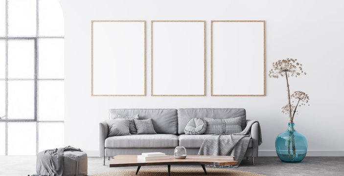 Frame mockup in interior living room design. Three vertical frames on white background with big window. modern grey sofa with plaid on, blue vase, and natural wooden table. Scandinavian home decor