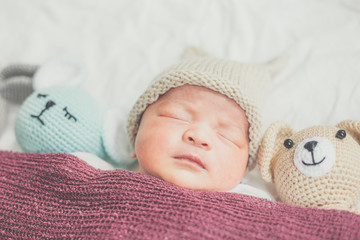 Adorable baby boy sleeping with many cute doll
