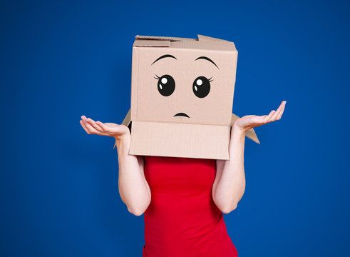 Person with cardboard box on its head and an expectant face expression stretching its hands out inquiringly on deep blue background