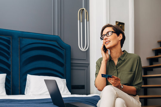 Mid adult woman talking on mobile phone and holding a credit card. Businesswoman making online order while sitting in a luxury apartment.