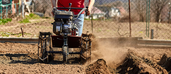 Gardener cultivate ground soil with tiller tractor or rototiller, cutivator