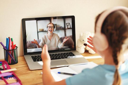 schoolgirl wearing headphones communicates via video link with an online teacher sitting at home