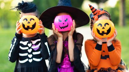 Happy Halloween! funny children in carnival costumes hide their heads behind buckets   pumpkins...