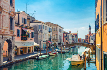 Chioggia cityscape with narrow water canal Vena with moored multicolored boats between old colorful buildings and brick bridge, blue sky background in summer day, Veneto Region, Northern Italy