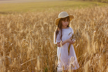 Photo sur Plexiglas Doux monstres Happy girl in a hat stands in a field of ripe rye in the sunset light. Ears of wheat.