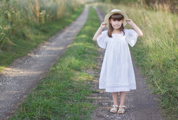 Beautiful girl in a hat stands on a road near field of rye. Little girl holds on to her hat