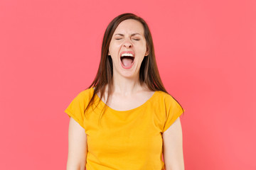 Crazy frustrated crying displeased young brunette woman 20s wearing yellow casual t-shirt posing standing screaming shouting keeping eyes closed isolated on pink color wall background studio portrait.