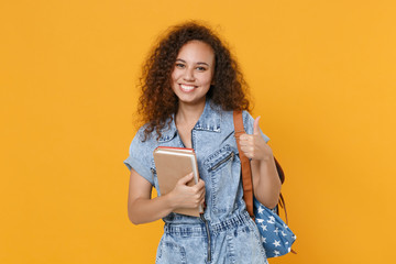 Smiling young african american girl student in denim clothes, backpack isolated on yellow...