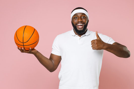 Excited young bearded african american fitness sports man basketball player in headband t-shirt playing basketball hold ball showing thumb up isolated on pastel pink color background studio portrait.