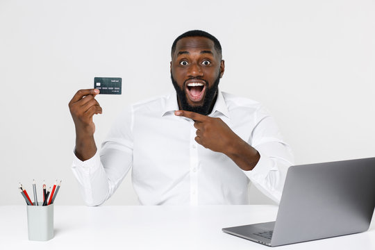 Shocked young african american male business man in white shirt posing working in office sitting at desk with laptop pc pointing index finger on credit bank card isolated on white color background.