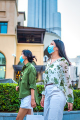 Two female friends Asian woman wearing face mask in outdoors shopping mall