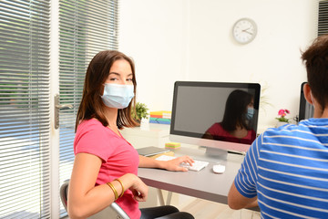portrait of beautiful young girl student in school classroom wearing a covid 19 surgical mask protection