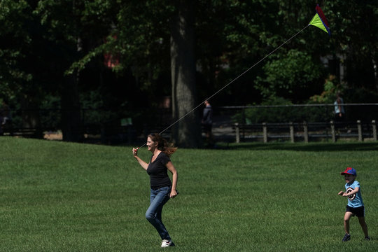 A woman and a child try to fly a kite in Central Park, in New York City